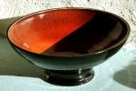 Handdrejad orange/svart skål på fot, stengods.