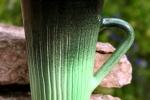 Randy lattemugg stengods. Blank grön/sv utvändigt, blank svart glasyr invändigt