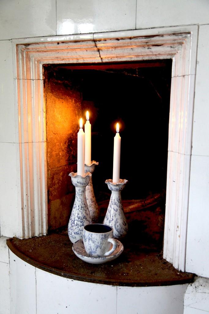 Drejade ljusstakar i den öppna spisen skapar trivsel.